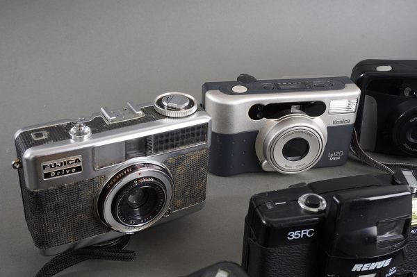a bunch of compact and small vintage cameras, as pictured