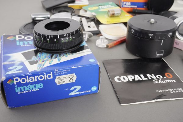 a bunch of various papers, caps, filters and camera – as per pictures