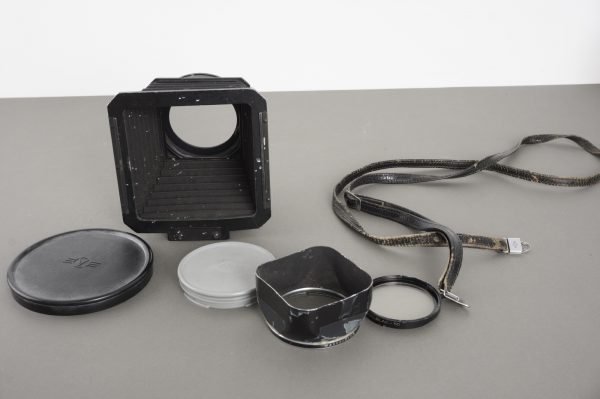 a bunch of worn Hasselblad accessories: hood, compendium, strap, filter, caps